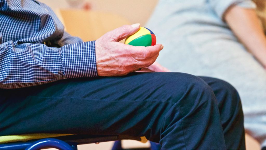 Senior holding a therapy ball